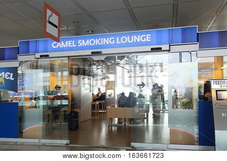 MUNICH, GERMANY - JULY 25, 2016: Camel Smoking lounge with passengers inside in Munich International Airport, Germany. Camel is sponsor of all smoking areas in german airports
