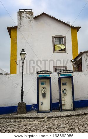 Telephone Boxes in front of White Facade in the Medieval Portuguese City of Obidos Call Box