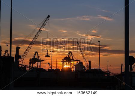 Silhouette of Cranes at Work in Boatyard at Sunset