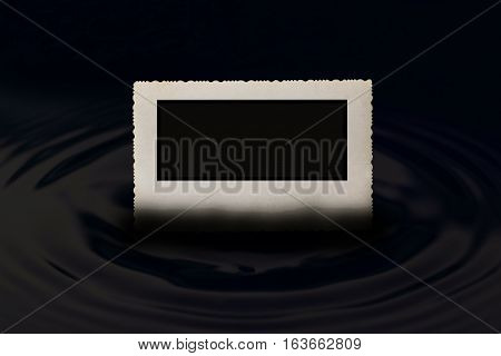 Front view of an old vintage photo frame with jagged edges horizontally partially submerged in the water which forms a circle wave in dark hues. Free place for your text is in the black rectangle in the photo.