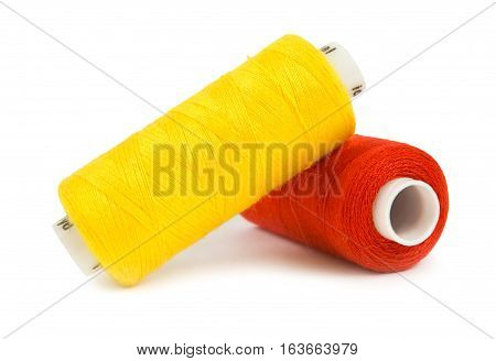Two spools of threads on a white background