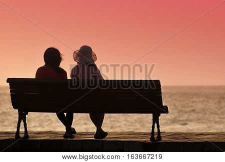Silhouette of two women on a bench by the sea