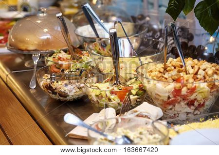 Bowls with various food in self service restaurant, closeup