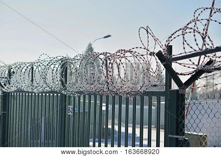 High metal fence with a sharp barbed wire on the top covered by snow in winter as a symbol of restricted access and protection of the area