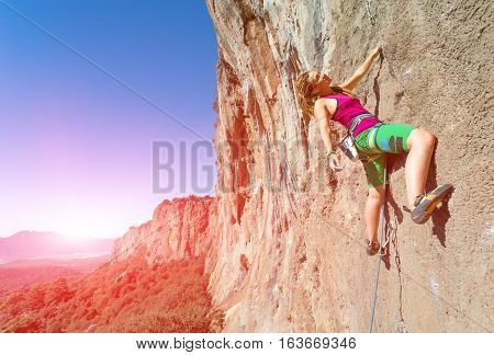 Youth female Rock Climber hanging on vertical Wall expressing Joy and Satisfaction Mountains Landscape and shining Sun on Background