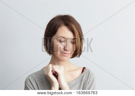 Shy And Beautiful Girl Looks Down Bashfully, Clutching Something In His Fists