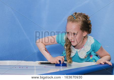 Girl intently and enthusiastically plays table hockey.