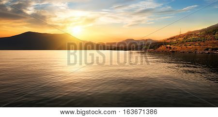 Calm sea and mountains at the beautiful sunset