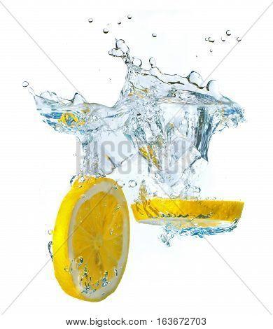 Lemon slices and ice cubes splashing water isolated on white background