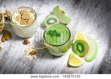 Healthy eating - green smoothie, oatmeal and nuts