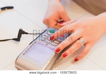 Closeup Of Girl's Hands Entering The Pin Code, Paying For The Purchase Banking Magnetic Card.