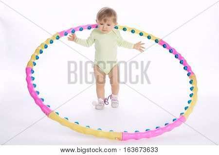 beautiful funny child plays with hoop on white