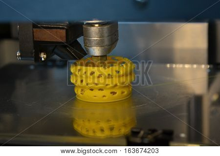 3D printer prints yellow form figure close. Automatic three dimensional 3d printer performs plastic modeling in laboratory. Plastic Wire Filament on 3D Printer. Modern printing technology.