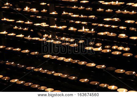 Praying memory candles in a temple in the dark. Butter candles burning in the temple for memories