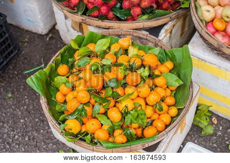 Asian Farmer Market Selling Fresh Mandarin In Hoi An, Vietnam. Orange And Green Colors.