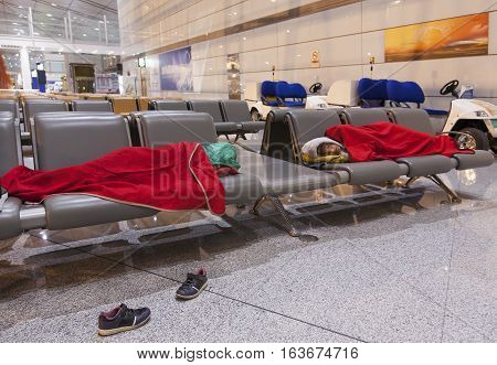 Mother and daughter sleeping on the airpot departure gates bench. Tireing travel concept.