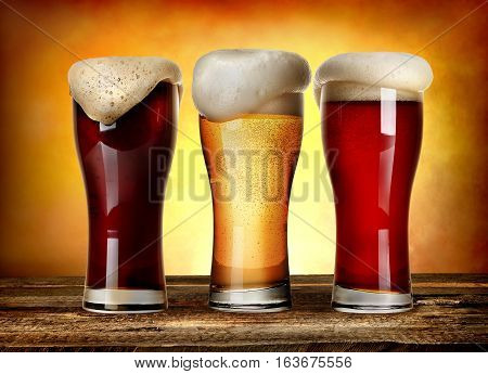 Three glasses of beer on a wooden table