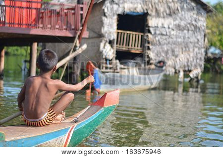 SIEM REAP CAMBODIA - November 2 2016: Child playing on a boat in a floating village on the bank of Tonle Sap Lake. Tonle Sap is the largest freshwater lake in SE Asia peaking at 16k km2