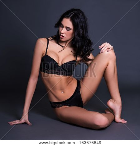 Portrait Of Sexy Young Woman In Black Lace Lingerie Sitting Over Dark Gray