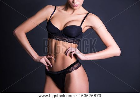 Close Up Of Sexy Female Body In Black Lace Underwear Over Dark Gray