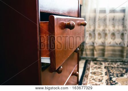Old wooden drawer with an extended drawer in the bedroom
