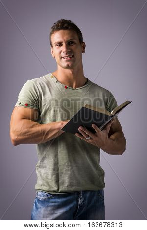 Handsome Sexy Muscular Man Reading Book, on Grey Background
