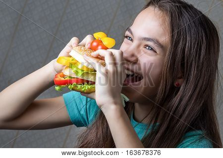 Portrait of a 11 year old girl eating a burger