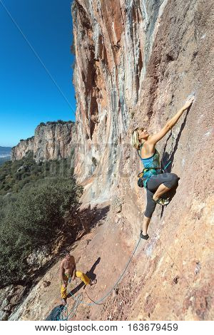 Female extreme Climber stepping up on high vertical Rock purposeful and sweeping Move and Face expression Mountains View and Summer Sky on Background