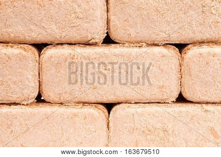 Briquettes made of sawdust lie on a white background. poster