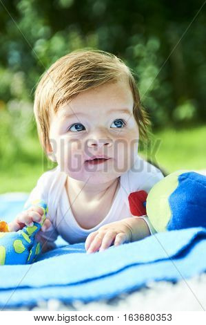 Newborn girl with blue eyes in the beautiful park outdoors, lies on a blanket and looking into camera