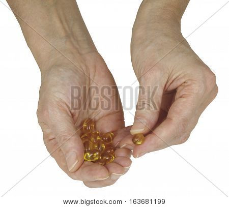 Are you getting your daily Cod Liver Oil - female hand holding golden colored vegetable capsules offering one isolated on a white background