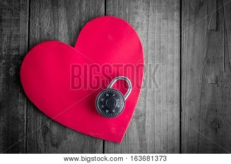 Read heart paper with combination padlock on grunge wood table
