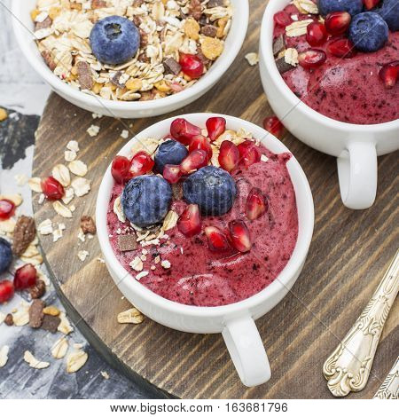 Healthy breakfast. Blueberry banana smoothie in a la carte dishes with granola and pomegranate on a marble background. selective focus