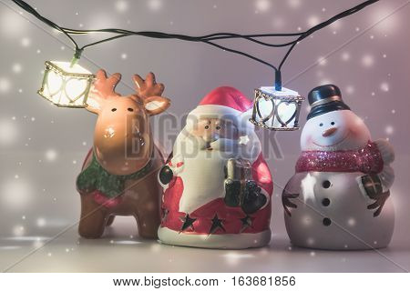 Santa Claus, Snowman And Reindeer With Light Bulb