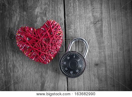 Read heart yarn with combination padlock on grunge wood table