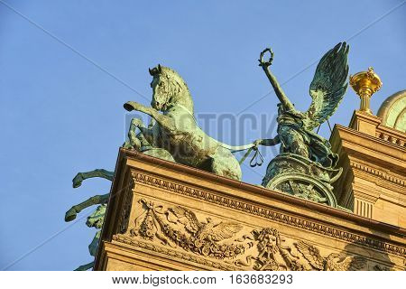 Bronze three horse chariot on top of Prague National Theater during sunset