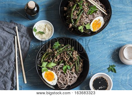 Pork green bean stir fry and soba noodles. On a wooden table top view. Flat lay