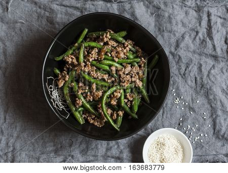Pork and green beans stir fry on a dark table top view
