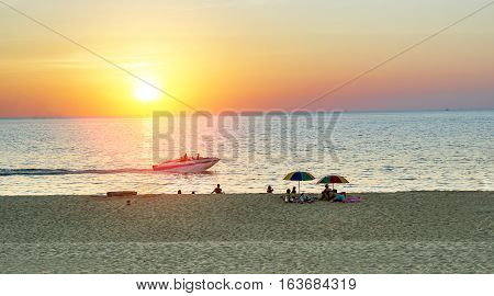Sunset view of people relaxing with the sun going down at kata beach in Thailand - Family and friends enjoying vacation in asian landscape - Holidays concept - Focus on people - Warm vivid filter