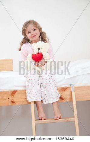 Cute girl in pyjamas hugging no-name teddy bear