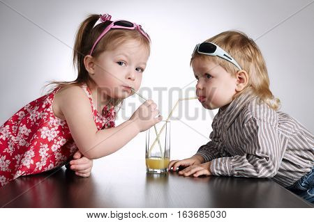 boy and girl drinking juice on bright background