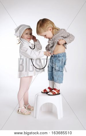 boy and girl playing doctor on white background