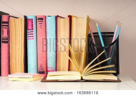 Open book stack of colorful hardback books on light table. Back to school. Copy space for text. Toned image.