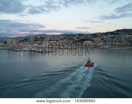Little Boat Accompanies The Cruise Ship In The Port