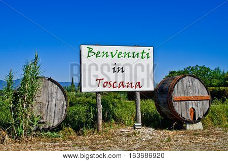 Billboard road surrounded by two wine barrels to welcome the tourists who come to visit Tuscany