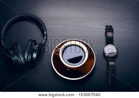 Cup of coffee on a dark table. Concept of business. Laptop, headphones, watch.