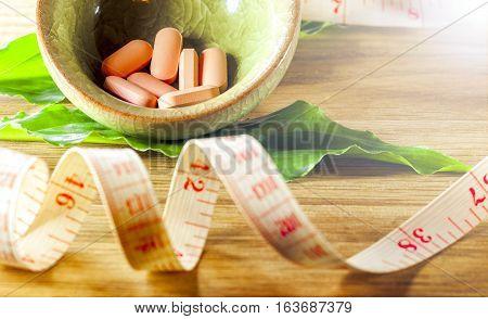 Dietary pills vie centimeter on wooden background. The concept of diet health