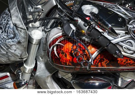 Classic chopper motorcycle with brake lever in the shape of brass knuckles and bodywork with aerography, fire sculls and celtic pattern