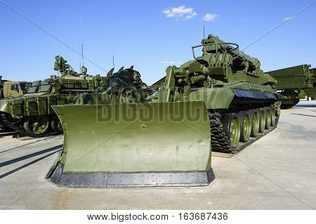 Military obstacle remover, combat engineering machine moulboard, army special-purpose cleaning vehicle, heavy industry, white clouds and blue sky on background