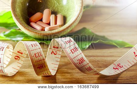 Dietary pills vie centimeter on wooden background. The concept of diet health